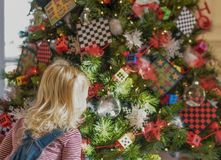 Weinig blond die meisje door verfraaide Kerstboom wordt gefascineerd Royalty-vrije Stock Afbeeldingen