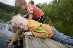 Weinig blond leuk meisje dat in water speelt Stock Afbeelding