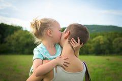 Weinig blond meisje die haar moeder kussen Stock Fotografie