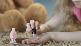 Weinig blond meisje die haar spijkers met roze poetsmiddel schilderen, spelend schoonheidssalon stock video