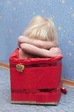 Weinig blond meisje in een doos Stock Foto