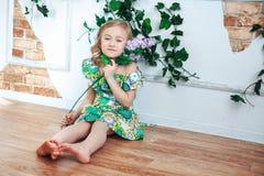 Weinig blond meisje in een heldere kleding in een ruimte die met bloemen wordt verfraaid Royalty-vrije Stock Foto's