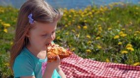 Weinig blond meisje eet pizza op kust op warme dag stock video