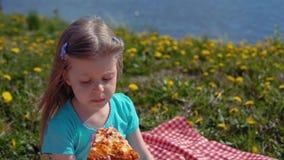 Weinig blond meisje eet pizza op kust op warme dag stock videobeelden