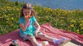 Weinig blond meisje eet pizza op kust op warme dag stock footage