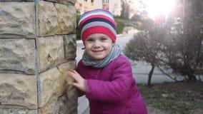 Weinig blond meisje komt uit uit achter de steenmuur en glimlacht stock footage
