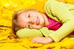 Weinig blond meisje legt op de bladeren van de de herfstesdoorn Stock Fotografie