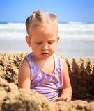 Weinig Blond Meisje zit in de Spelen van het Zandgat op Strand Stock Foto's