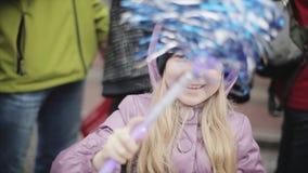 Weinig blonde glimlachend meisje die blauwe pom in camera golven pom Mensen Sportevenement stock videobeelden