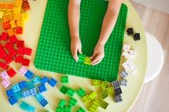 Weinig blonde jong geitjejongen die met veel kleurrijk plastic blok spelen royalty-vrije stock fotografie