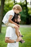 Weinig blonde jongen die een witte t-shirtzitting op de schouders van zijn knappe gebaarde vader dragen royalty-vrije stock afbeelding