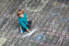 Weinig blonde jongen die met kleurrijk krijt in openlucht schilderen Stock Foto