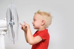 Weinig blonde jongen in een rode t-shirt raakt de ventilator met zijn vinger Het concept van de zomer royalty-vrije stock fotografie