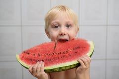 Weinig blonde jongen eet een grote brok van watermeloen Het concept van de zomer Het binnenland van het huis royalty-vrije stock afbeelding