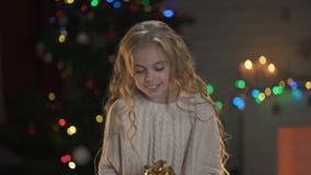 Weinig blonde meisjesholding huidig onder Kerstboom, magische de winteratmosfeer stock footage