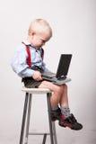 Weinig blondejongen zit op stoel met draagbare dvdspeler Stock Afbeeldingen