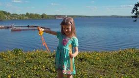 Weinig blondemeisje blaast grote zeepbels tegen achtergrond van overzeese kust op stock videobeelden