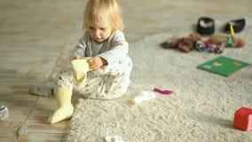 Weinig blondemeisje die sokken proberen aan te zetten stock footage