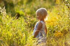 Weinig blondemeisje in kleding onder wildflowers Royalty-vrije Stock Afbeeldingen