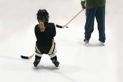 Weinig blondemeisje speelt hockey in volledig materiaal met papa De foto is genomen uit de rug stock foto