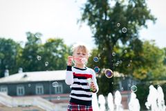 Weinig blondy meisje die met zeepbels in de zomerpark spelen Royalty-vrije Stock Afbeelding