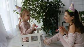 Weinig blondy meisje en haar moeder blazen feestelijke hoornen stock videobeelden