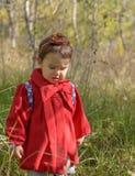 Weinig boos verstoord meisje in een rode jasjetribunes alleen in Stock Foto's