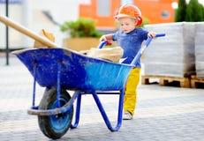 Weinig bouwer in bouwvakkers met kruiwagen die in openlucht werken Stock Foto's