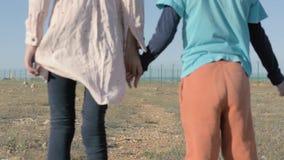 Weinig broer en zustervluchtelingen handen houden die zich bevindt onder woestijn op staatsgrens stock videobeelden
