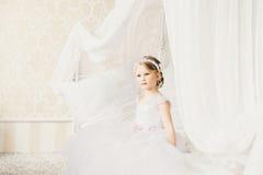 Weinig bruidzitting op het bed Stock Foto
