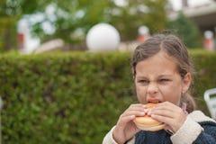 Weinig caucasiangirl die hamburger eten, die neer eruit zien Stock Foto's