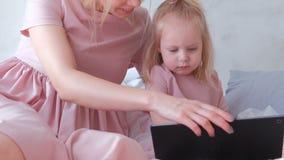 Weinig charmant blond meisje selecteert een toepassing op tablet met haar mamma stock video