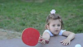 Weinig charmant gelukkig meisjeskind speelt pingpong op de straat stock video