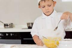 Weinig chef-kok die de consistentie van zijn beslag controleren royalty-vrije stock foto
