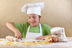Weinig chef-kok die de deegbereidingsdeegwaren snijdt Royalty-vrije Stock Foto