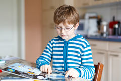 Weinig de lezingsboek van de jong geitjejongen op school Stock Foto