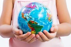 Weinig de Wereldbol van de Jong geitjeholding op Haar Handen Royalty-vrije Stock Afbeelding