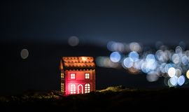 Weinig decoratief huis, mooi feestelijk stilleven, leuk plattelandshuisje bij nacht, echte bokehachtergrond van de Nachtstad, de  stock afbeelding
