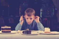 Weinig die jongen door een assortiment van cakes wordt gefascineerd royalty-vrije stock foto's