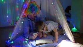 Weinig die jongen heeft pret met clown en leest sprookjes zittend in tent met heldere slinger binnen wordt verfraaid stock footage