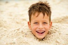 Weinig die jongen in het zand op strand wordt begraven stock foto