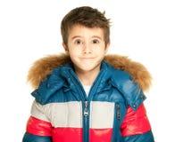 Weinig die jongensportret in de winterjasje op wit wordt geïsoleerd Stock Fotografie