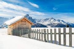 Weinig die plattelandshuisje met sneeuw in de hoge Dolomietbergen wordt behandeld Stock Afbeeldingen