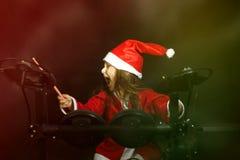 Weinig die slagwerker als Santa Claus wordt vermomd die de elektronische trommeluitrusting spelen Stock Foto's