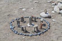 Weinig die Stonehenge van stenen op het strand wordt gemaakt stock foto