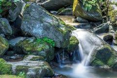 Weinig die waterval door reusachtige rotsen wordt omringd Stock Foto