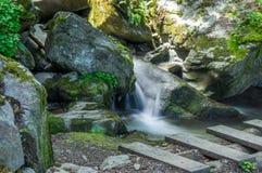 Weinig die waterval door reusachtige rotsen wordt omringd Stock Fotografie
