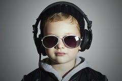 Weinig DJ grappige jongen in zonnebril en hoofdtelefoons Het luisteren van het kind muziek in hoofdtelefoons deejay Stock Fotografie
