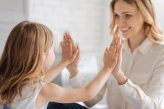 Weinig dochter die haar handgrootte vergelijken met mums stock fotografie