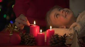 Weinig dochter die hoe Kerstmiskaarsen van de moederverlichting, geloof in mirakel kijken stock video